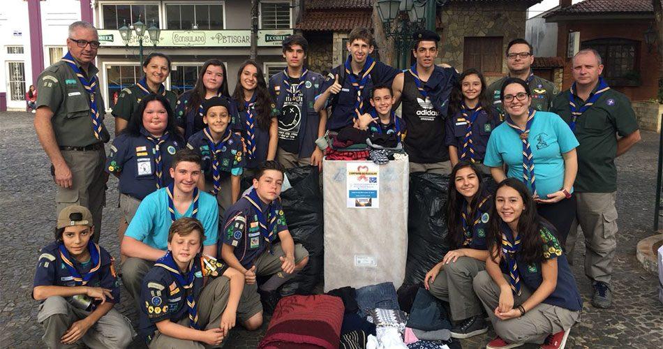 Grupo de escoteiros doa roupas para a Campanha do Agasalho